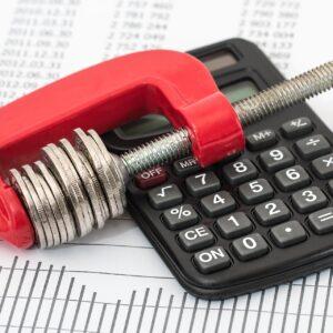 Symbolbild mit Taschenrechner, Geldschraube und Zahlenblatt im Hintergrund
