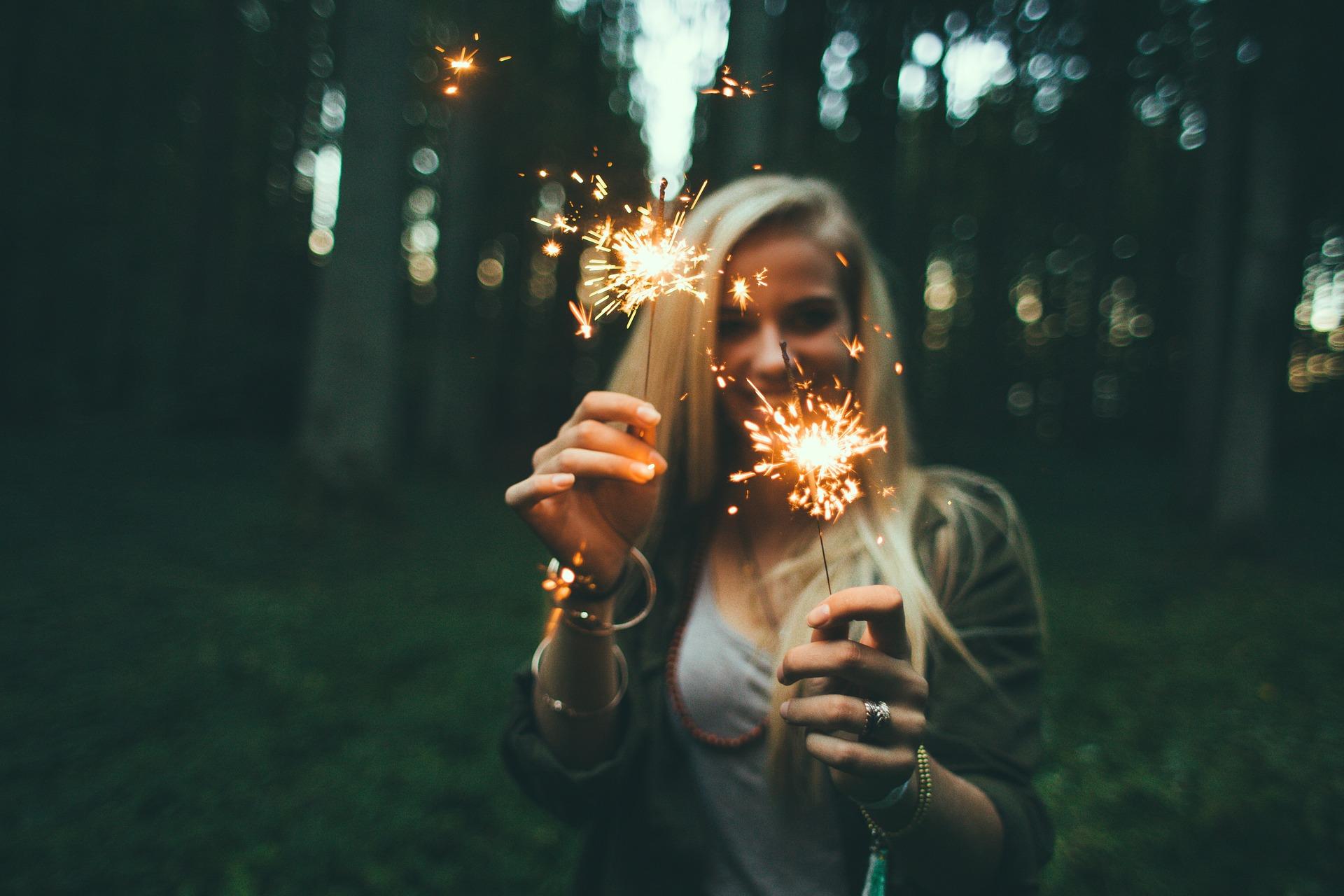 Junge Frau mit Wunderkerzen vor einem Wald