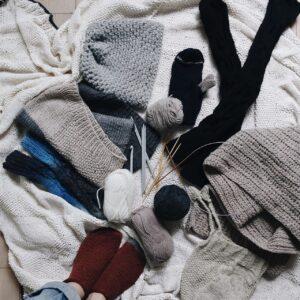 Verschiedene Strickwaren von Socken bist Mütze von oben fotografiert